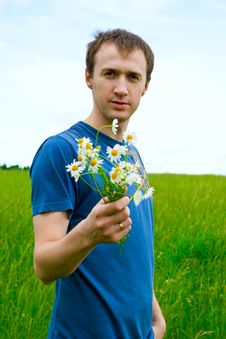 Free The Young Man With Camomiles On Green Meadow Royalty Free Stock Photography - 20070397