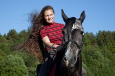 Beautiful Girl With Brown Hair On A Black Horse Stock Image