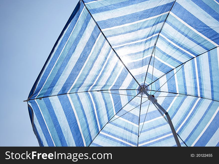Blue Backlit Parasol Against Plain Sky