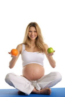 Free Pregnant Woman Practicing Yoga And Keeps Fruit Stock Image - 20139791