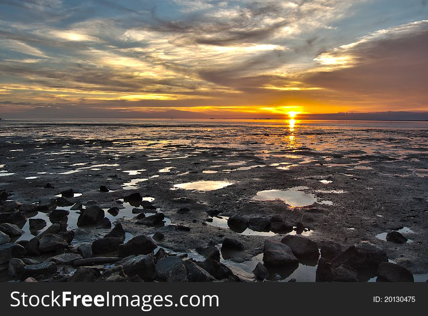 The sea side golden sunset during low tide