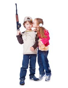 A Girl Is Kissing A Boy With The Gun Royalty Free Stock Images