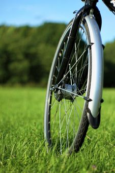 Front Bike Wheel On The Grass Field Royalty Free Stock Photos