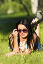 Free Beautiful Brunette In Sunglasses Lying On Grass Royalty Free Stock Photography - 20226097
