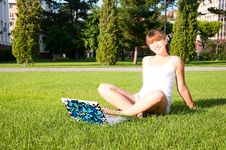Young Girl Sitting In The Park With Your Laptop Stock Photography