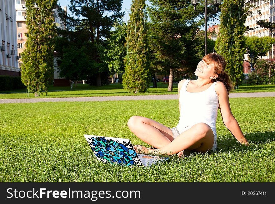 Young girl sitting in the park with your laptop