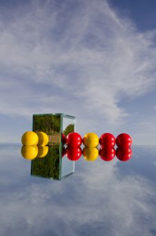 Red And Yellow Balls On Mirror And Sky Stock Photography