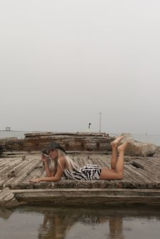 Girl In A Hat Lying On Broken Ship Royalty Free Stock Photography