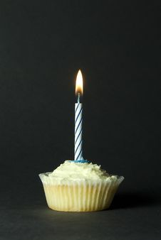 Cupcake With Blue Candle On Black Background Royalty Free Stock Photography