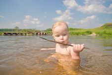 Free Adorable Baby Sit In River And Play With Wood Royalty Free Stock Image - 20312456