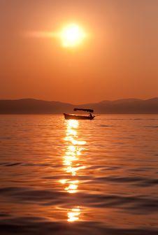 Fishermen Crossing A Lake At Sunset Stock Photography