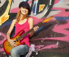 Girl With Guitar And Graffiti Wall Stock Photo
