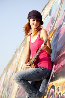 Girl With Guitar And Graffiti Wall Royalty Free Stock Photography