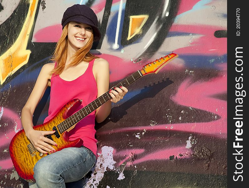 Girl with guitar and graffiti wall