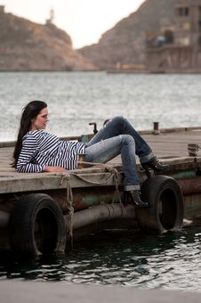 Woman Lying On A Pier In The Background Of The Sea Stock Photography