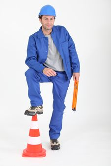 Free Builder With Foot On Traffic Cone. Stock Photos - 20430113