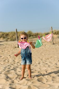 Little Baby Is Hanging Laundry On The Beach Stock Photo