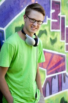 Teen Boy With Earphones Near Graffiti Wall. Royalty Free Stock Image