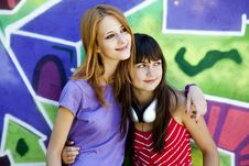 Two Girlfriends Near Graffiti Wall. Royalty Free Stock Photo