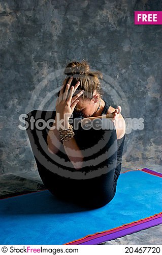 Woman doing yoga exercise Womb pose Stock Photo