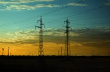 Electricity Pillars And Wind Turbines On Sunset Stock Image