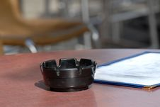 An Ashtray And Menu In A Sidewalk Cafe Dining Area Stock Photography