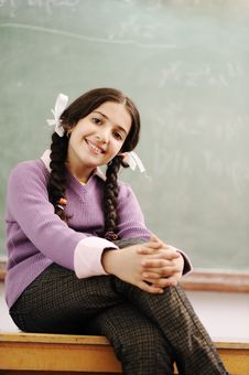 Free Cute Schoolgirl Siting On Desk Royalty Free Stock Photography - 20516607