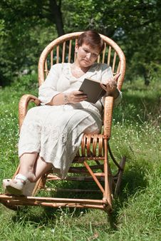 Free Mature Woman Reading Book In Rocking Chair Stock Photo - 20530120