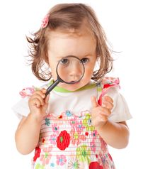 A Little Girl Is Looking Through The Loupe Stock Photo