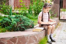Free Young Girl With Bagpack Reads Waiting For School Stock Photos - 20576353