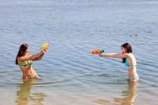 Free Two Girls In Bikini Play With A Water Guns Royalty Free Stock Image - 20577056