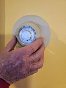 Free Elderly Mans Hand Turns Up Wall Thermostat Royalty Free Stock Photography - 205791257