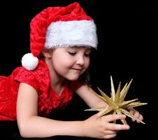 Girl In Christmas Outfit Playing With Golden Star Royalty Free Stock Photo