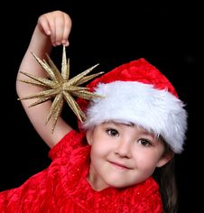 Girl In Christmas Hat Playing With Golden Star Royalty Free Stock Photography