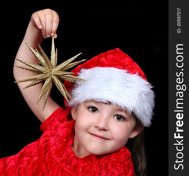 Girl in Christmas hat playing with golden star