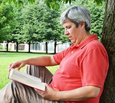 Free Middle-aged Woman Reading Book By Tree Royalty Free Stock Photography - 20625727