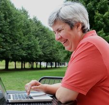 Free Middle-aged Woman Browsing On Laptop Outside Stock Photos - 20625763