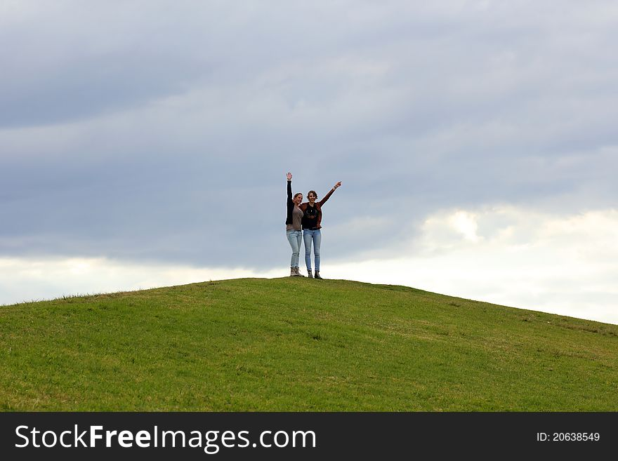 Two women on top of green hill waving