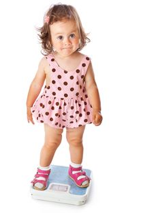 A Little Girl Is Standing On The Scales