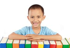 Young Boy Smiling On Top Of His Books Royalty Free Stock Image