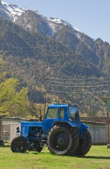 Blue Tractor In The Background Of The Mountains Stock Photography