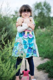Cute Child Girl Poses With Baby Doll And Scooter Royalty Free Stock Images