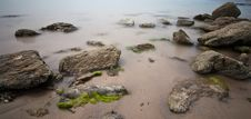Long Exposure Of Rocks On Wet Sand Royalty Free Stock Photos