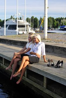 Two Girls Resting On The Pier Royalty Free Stock Photos