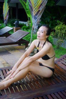 Woman In Black Bikini Sitting On Bank Royalty Free Stock Images