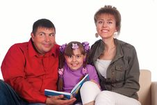 Daughter Reads With Parents Stock Photos