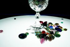 A Pile Of Hand Made Beads Around A Glass Goblet Royalty Free Stock Photo