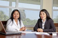 Free Two Asian Women At Desk With Laptop Royalty Free Stock Photography - 20701787
