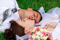 Free Happy Bride And Groom Lying On A Green Grass Royalty Free Stock Images - 20713859