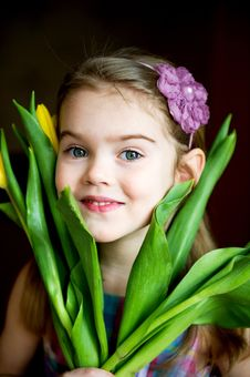 Portrait Of Adorable Sunny Child Girl With Tulips Stock Images